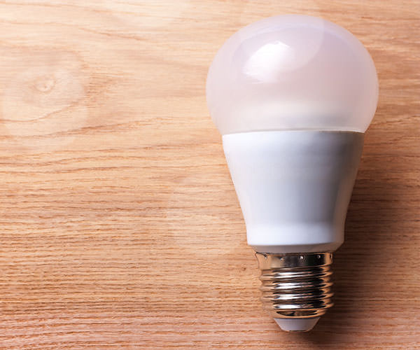 Image of LED bulb on wooden background